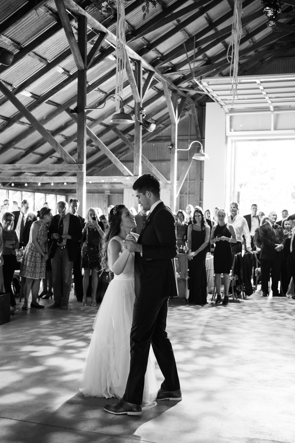 The gorgeous couple takes their first dance during their airy barn reception venue as dusk falls outside; photo by Sylvie Gil
