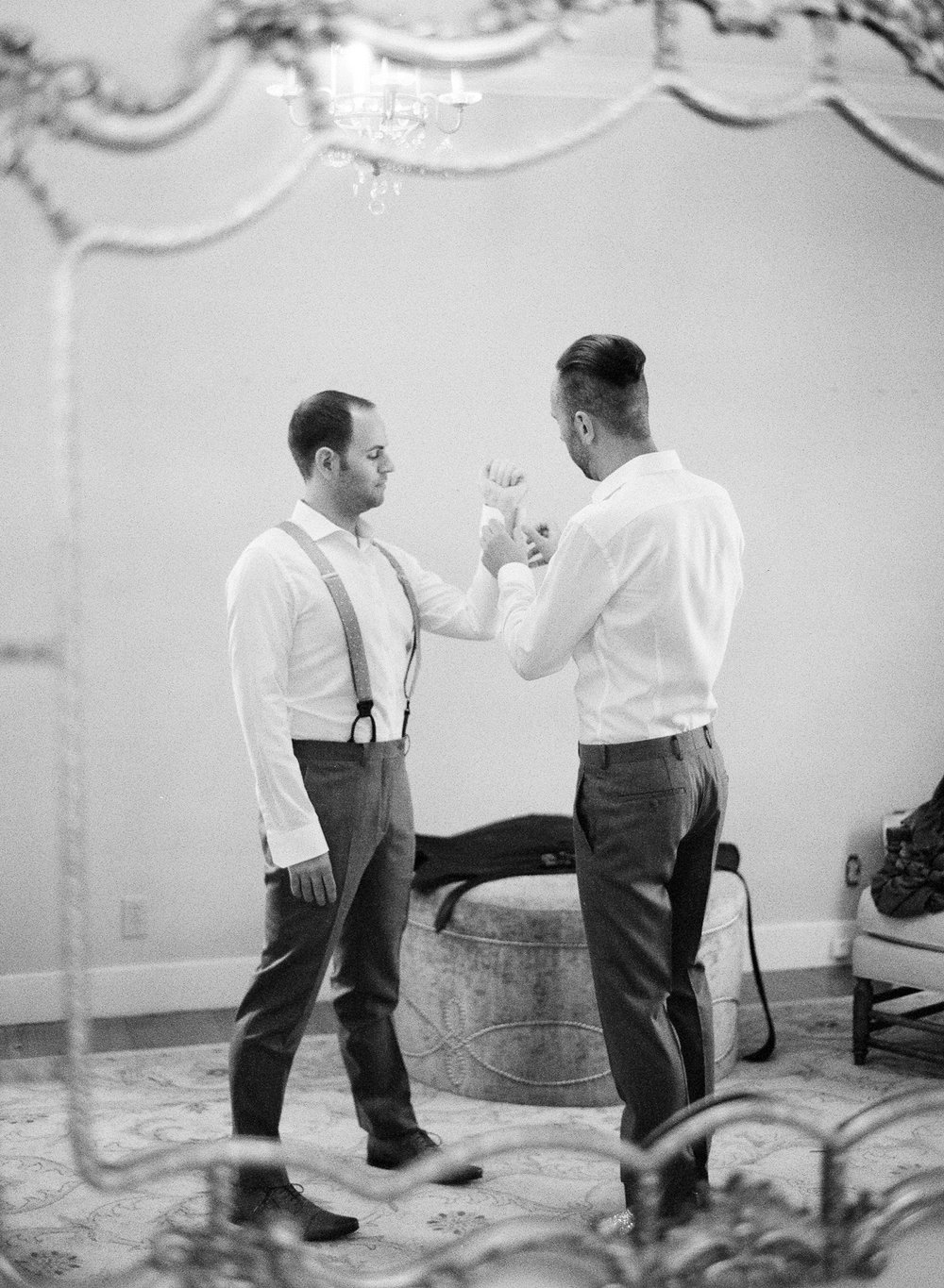 Grooms help each other get ready for the wedding ceremony; Sylvie Gil Photography