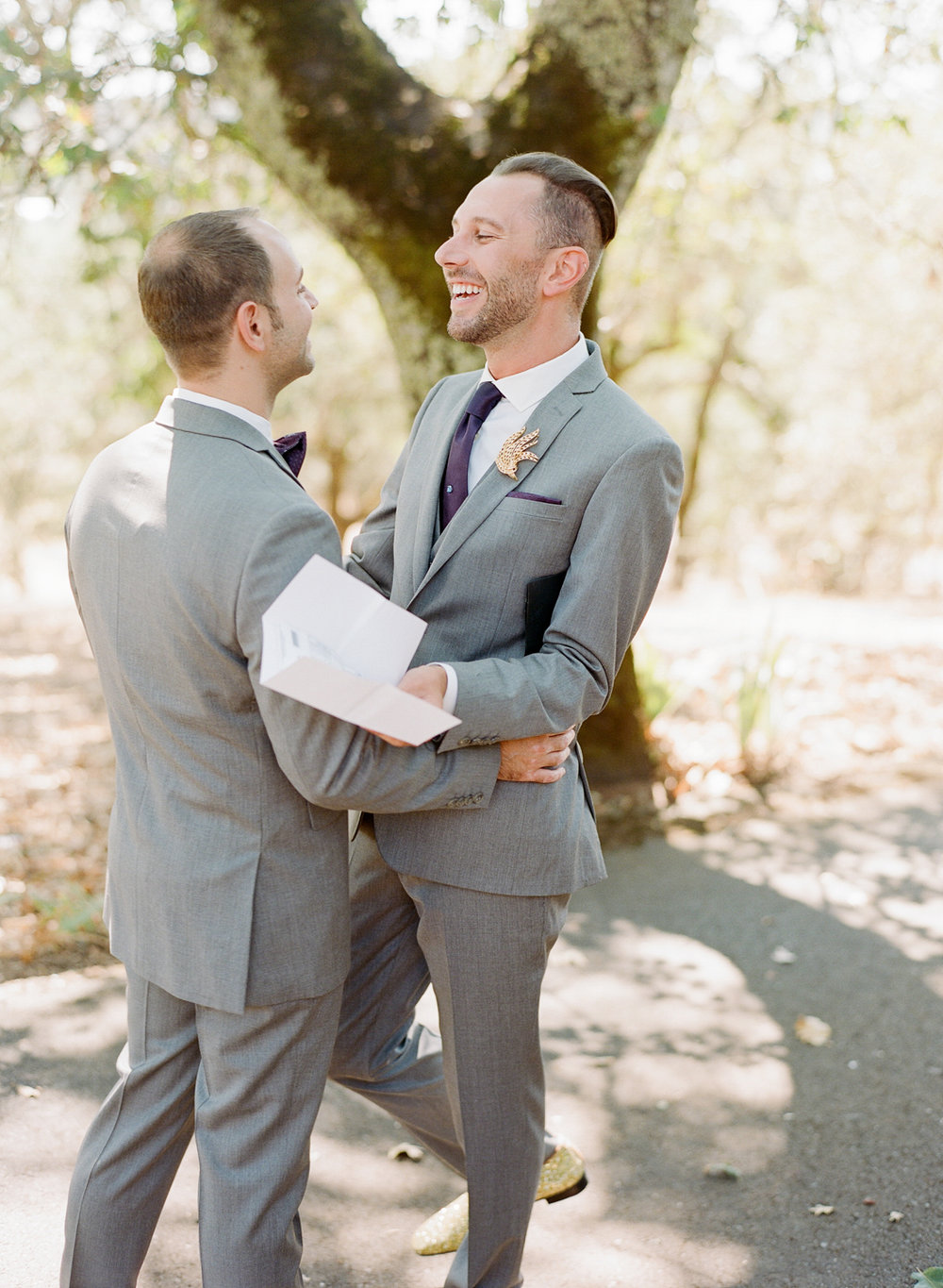 Grooms embrace after reading first look letters before ceremony at Kunde Winery; Sylvie Gil Photography