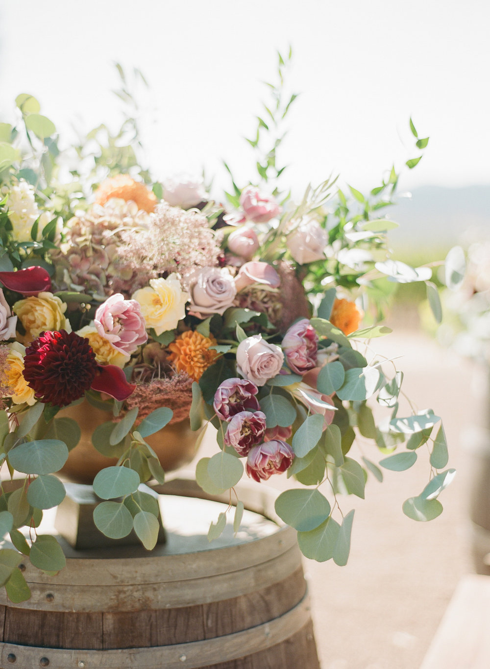 Eucalyptus studded floral arrangements on decorative barrels at the ceremony space; Sylvie Gil Photography