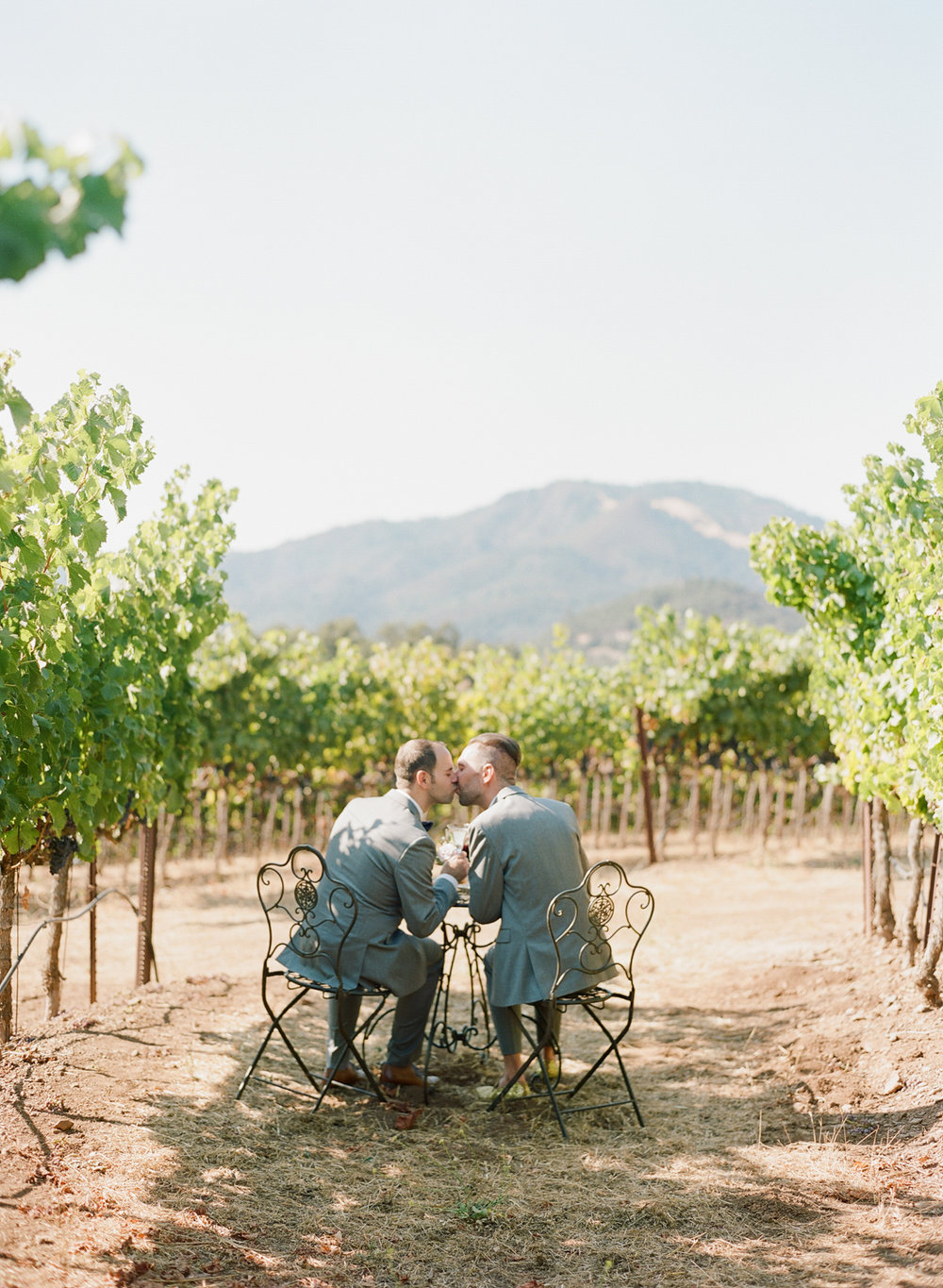 Sweet gay couple shares a kiss after their wedding ceremony in Kunde Winery, Napa Valley; Sylvie Gil Photography