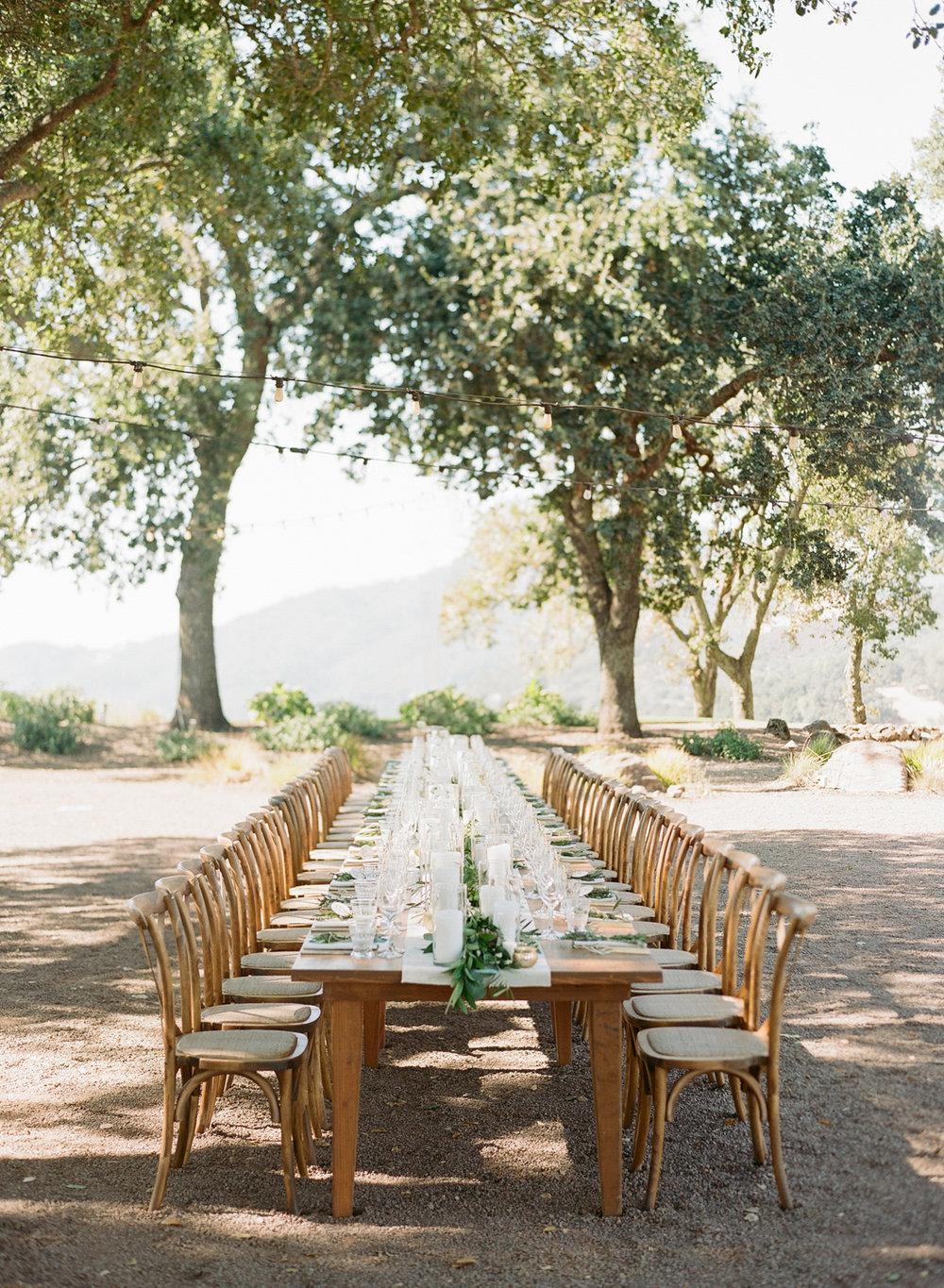 Single reception table set under string lights at Kunde Winery in Napa Valley; Sylvie Gil Photography