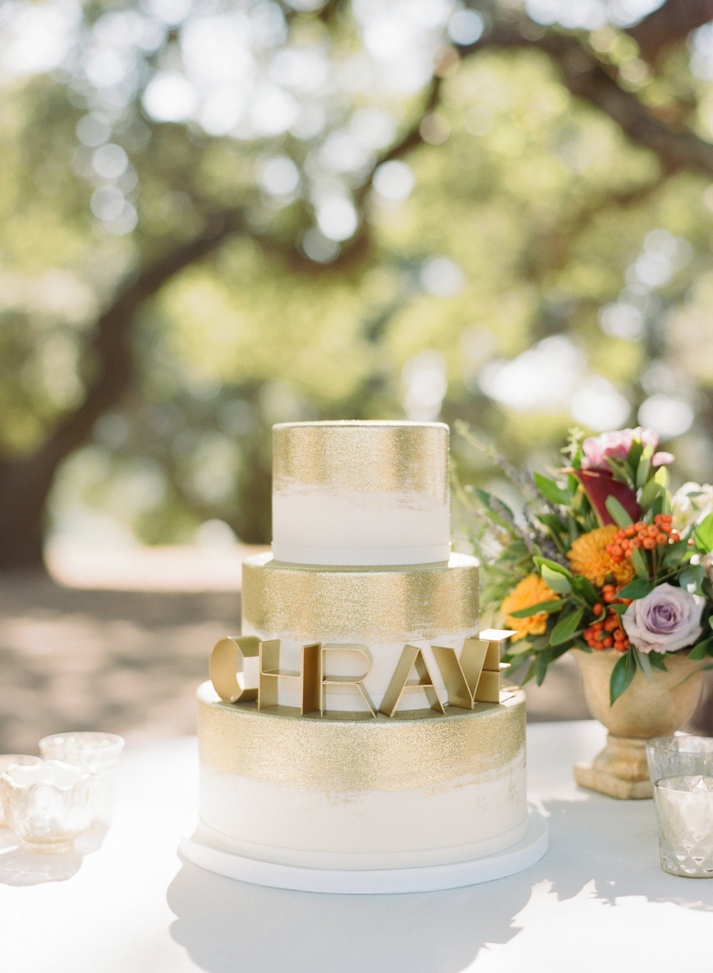 Gold-painted, three-tier cake with art deco cake topper; Sylvie Gil Photography