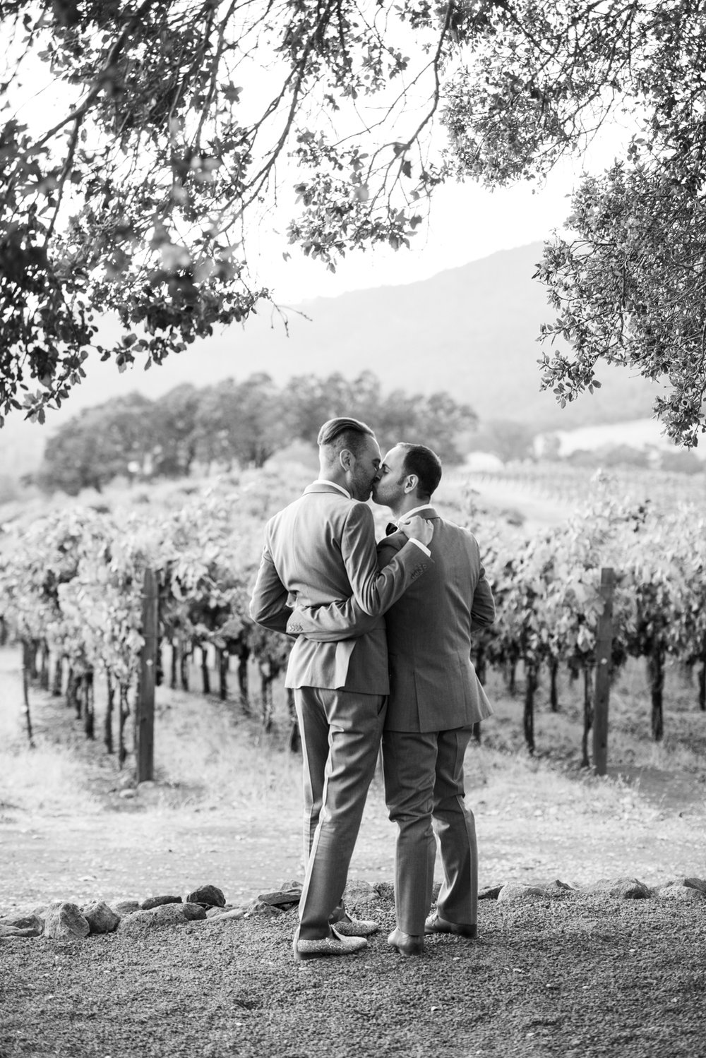 Grooms share a kiss before the vineyards at Kunde Winery; Sylvie Gil Photography