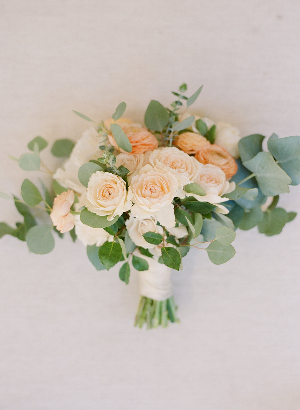 Eucalyptus leaves and pale pink and orange ranunculus bouquet; Sylvie Gil Photography