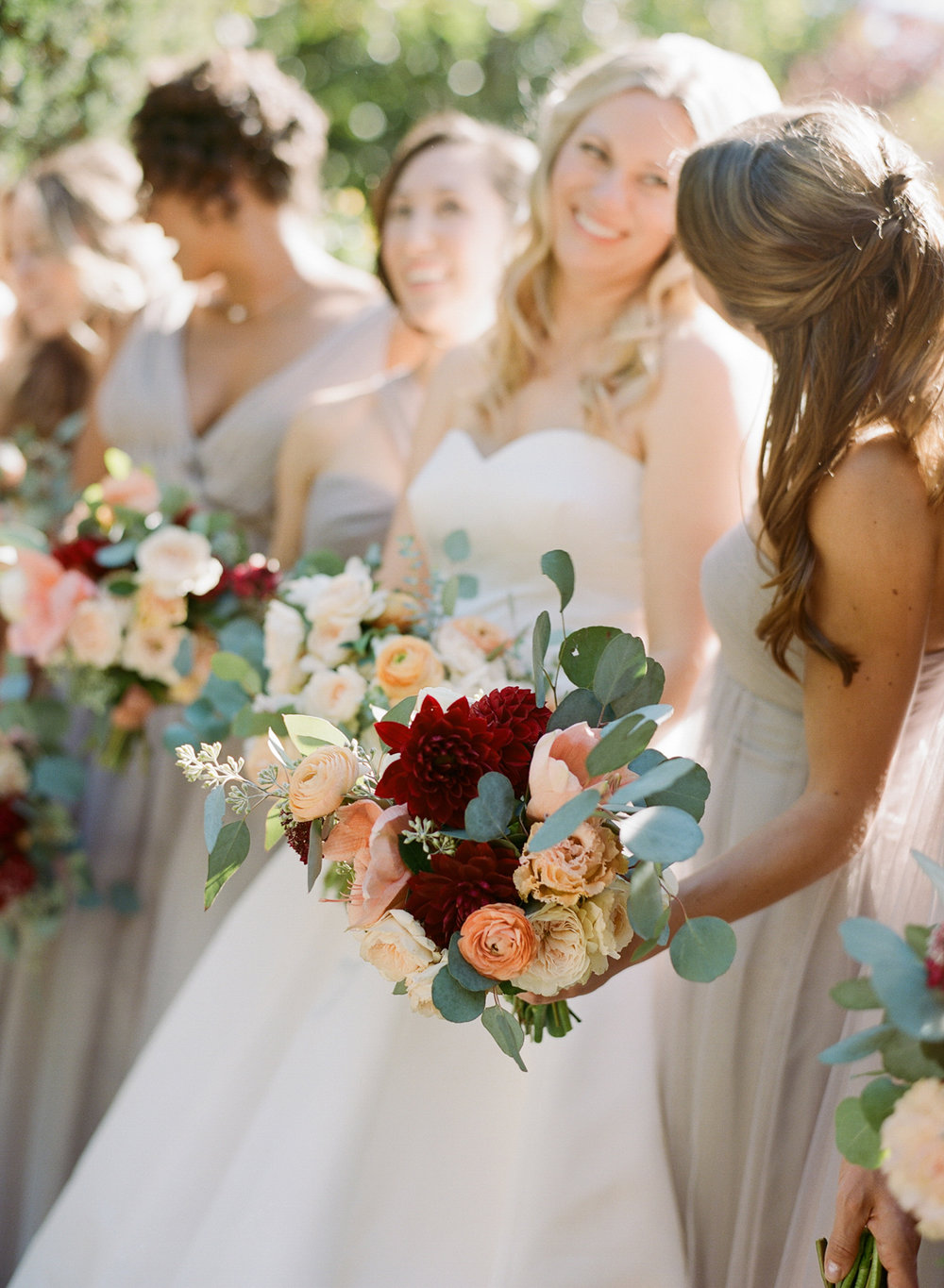 Bridesmaids' bouquets with burgundy dahlias and peach ranunculus; Sylvie Gil Photography