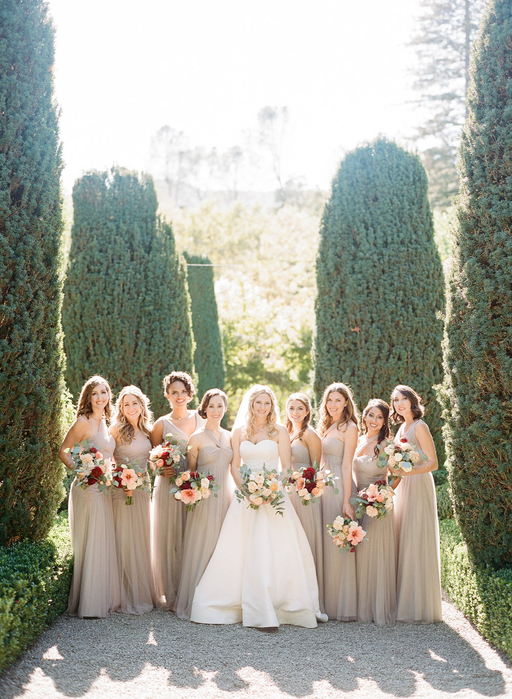 Bridesmaids with mixed-styles taupe gowns and autumny bouquets; Sylvie Gil Photography