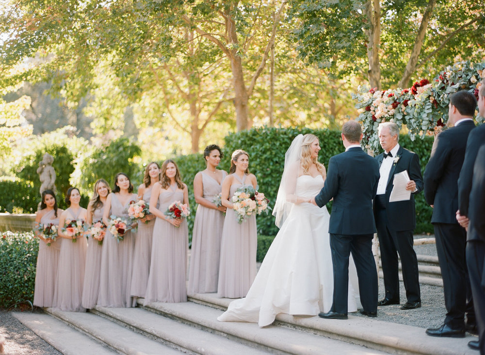 The wedding party stands on the steps at Beaulieu Gardens during the ceremony; Sylvie Gil Photography