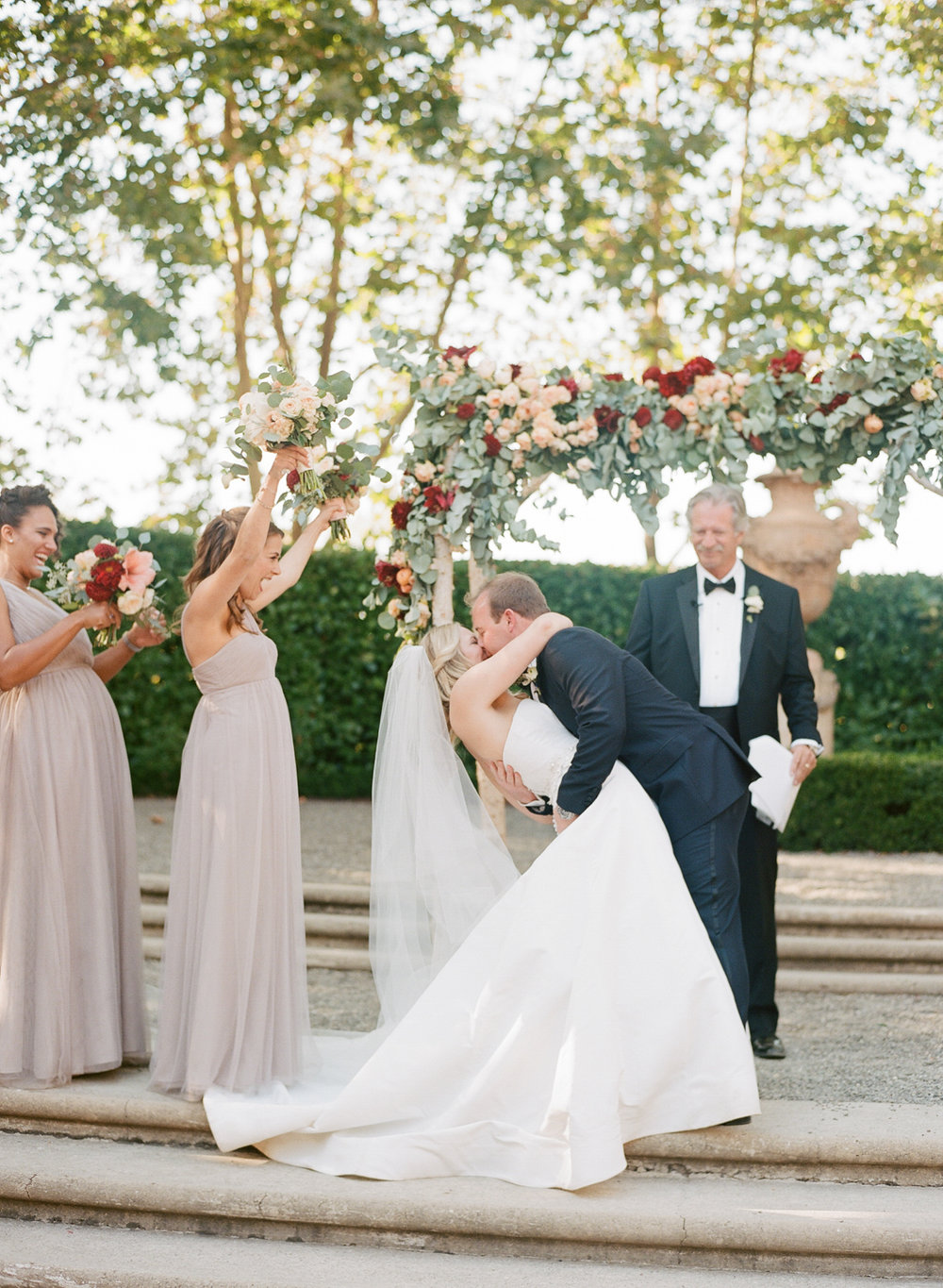 The groom dips the bride for their first kiss during their wedding ceremony at Beaulieu Gardens; Sylvie Gil Photography