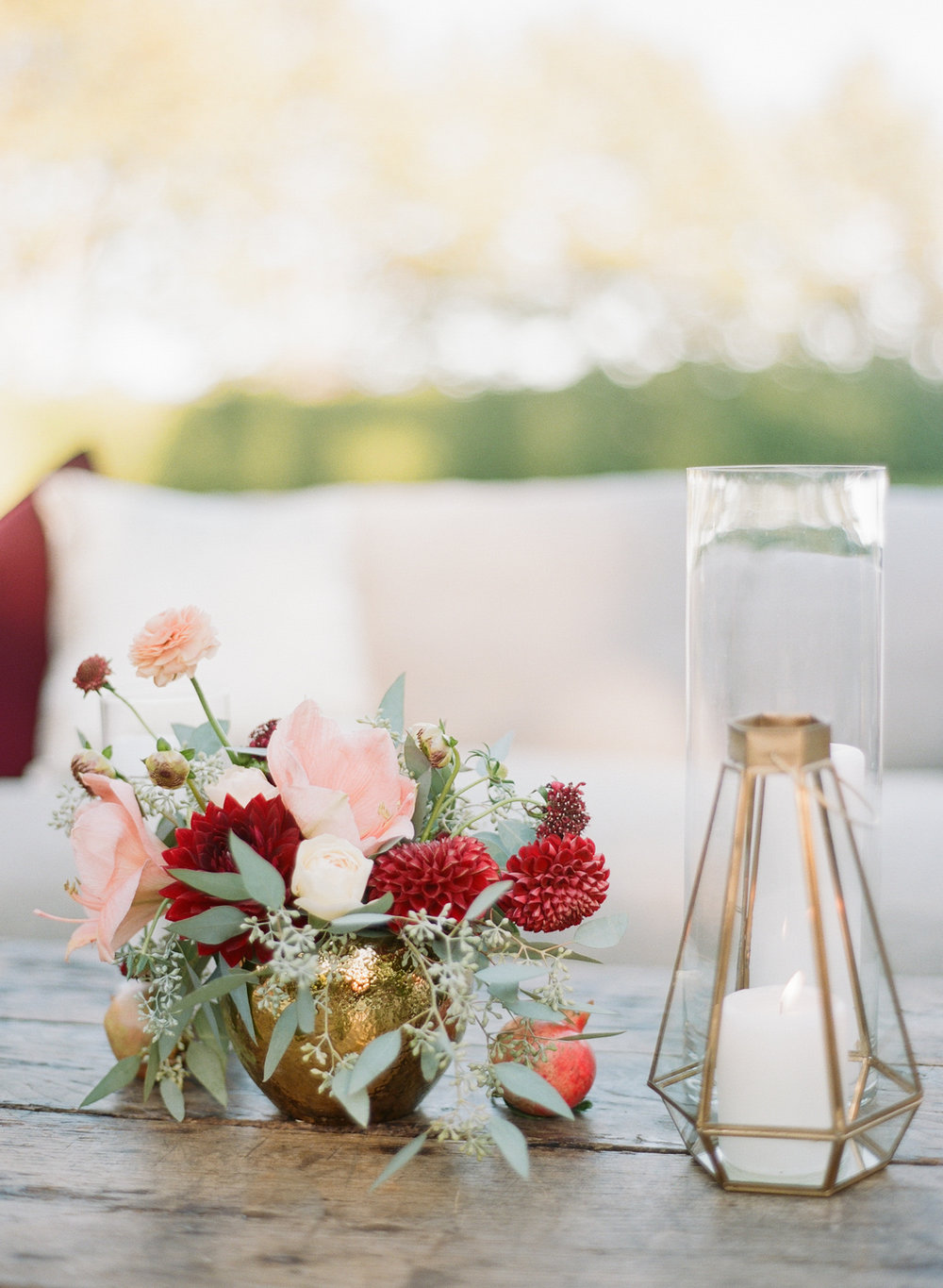 Burgundy and pink floral accents and art deco lanterns decorate the reception space; Sylvie Gil Photography