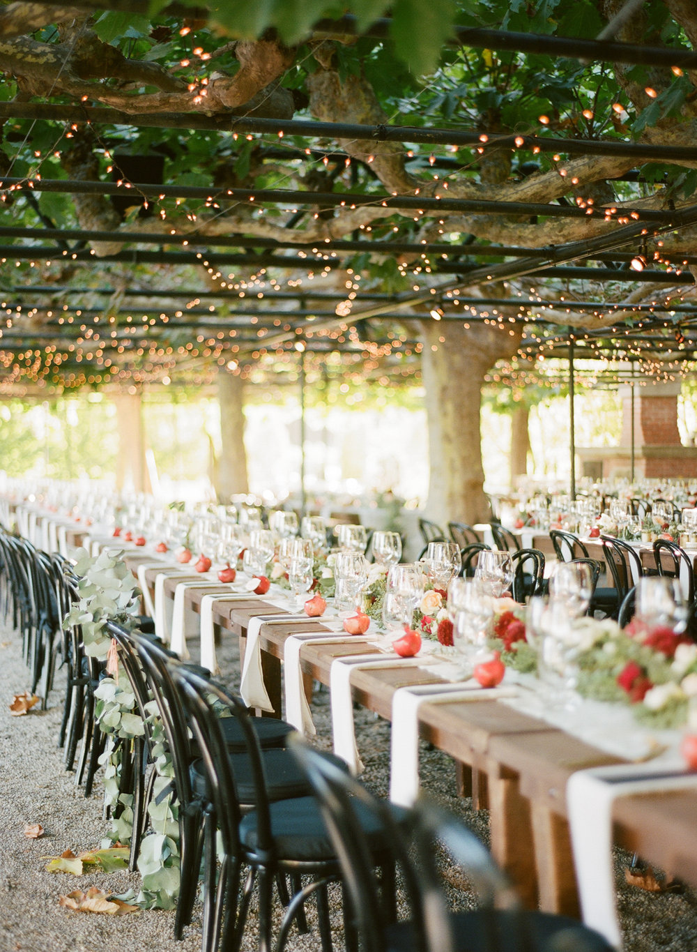 Long reception tables set up below tree arbors and criss-crossed string lights; Sylvie Gil Photography
