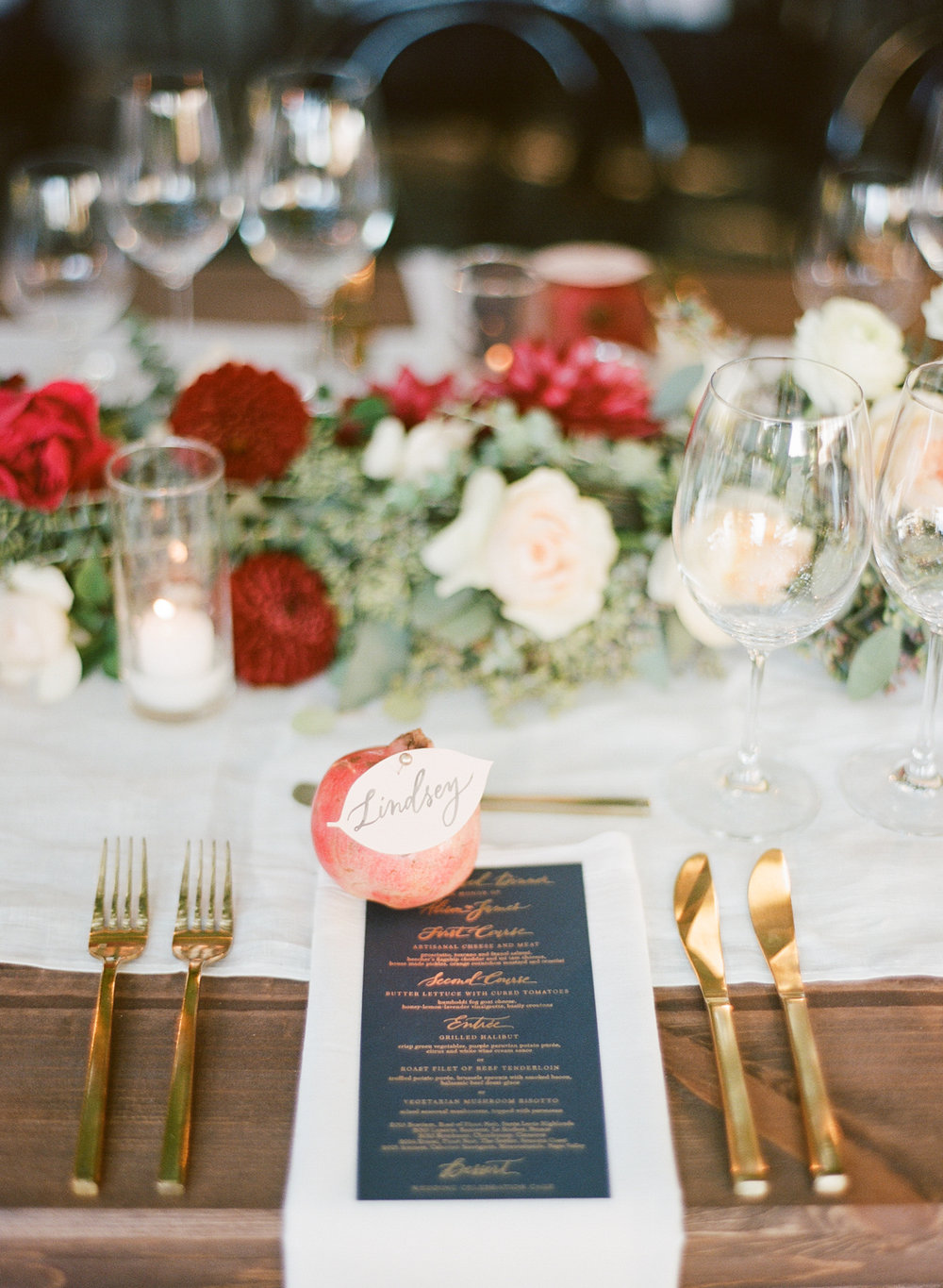 Gold cutlery and placecards pinned to pomegranates decorate the reception table; Sylvie Gil Photography