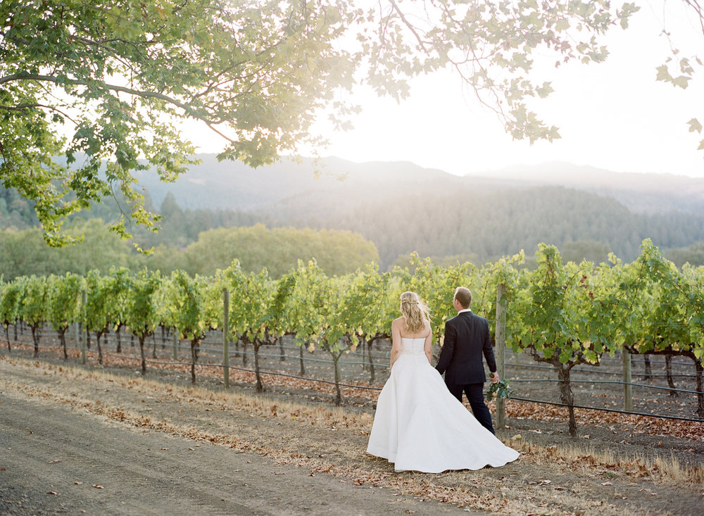 The newlywed couple takes a stroll through vineyards in the hills of St. Helena during a couple session; Sylvie Gil Photography
