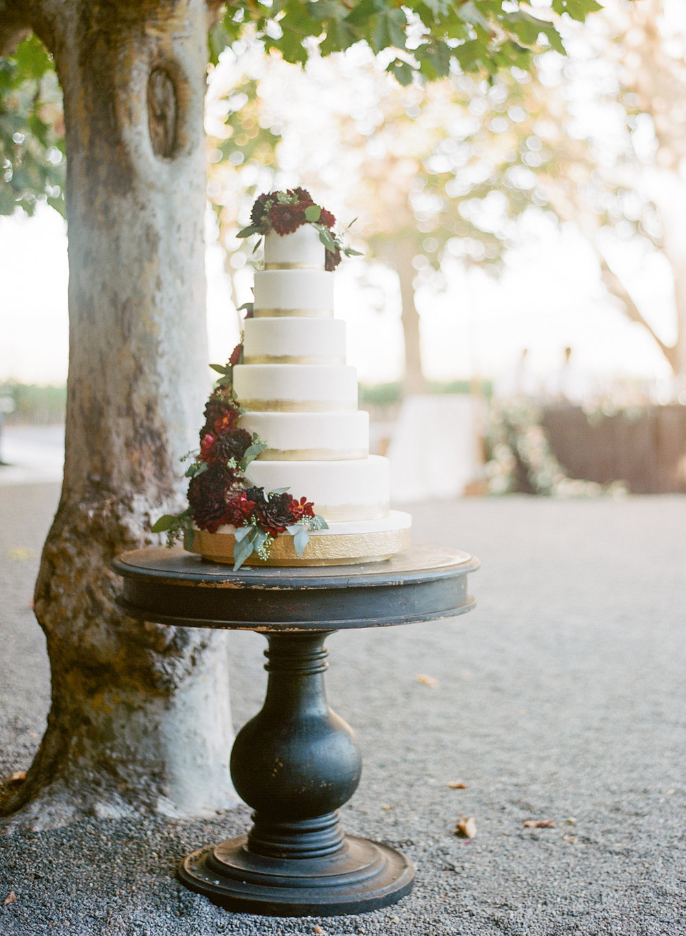 A six tier cake trimmed with gold and a wraparound garland of burgundy dahlias sits on a vintage cake stand; Sylvie Gil Photography