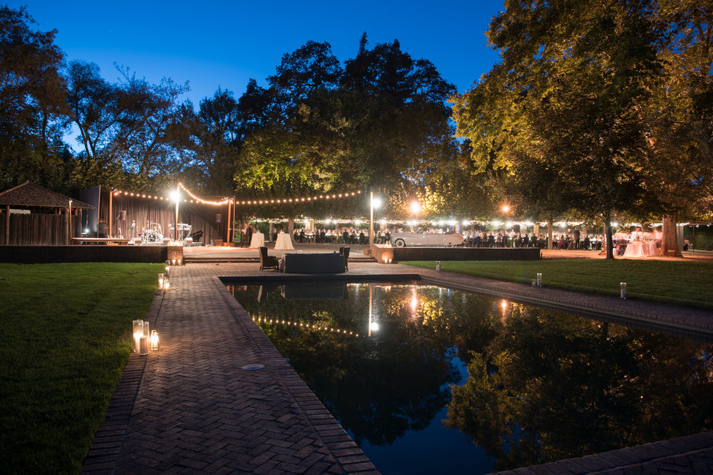 Night falls over the outdoor wine country wedding reception at Beaulieu Gardens; Sylvie Gil Photography