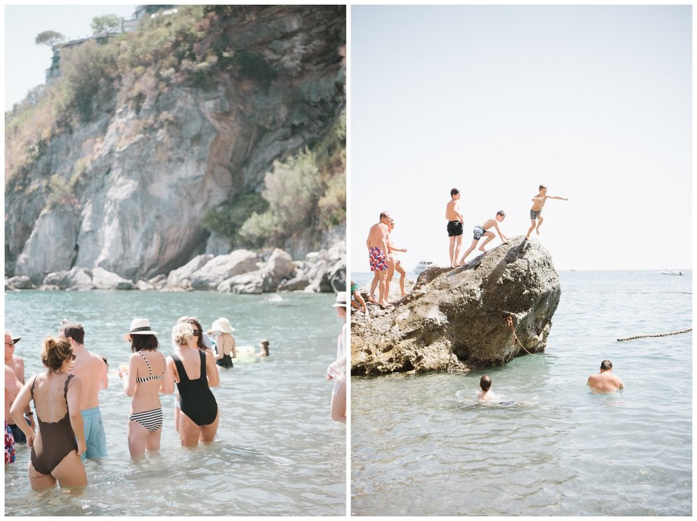 Kids jump off a rock in the water outside the Positano beach club; Sylvie Gil Photography