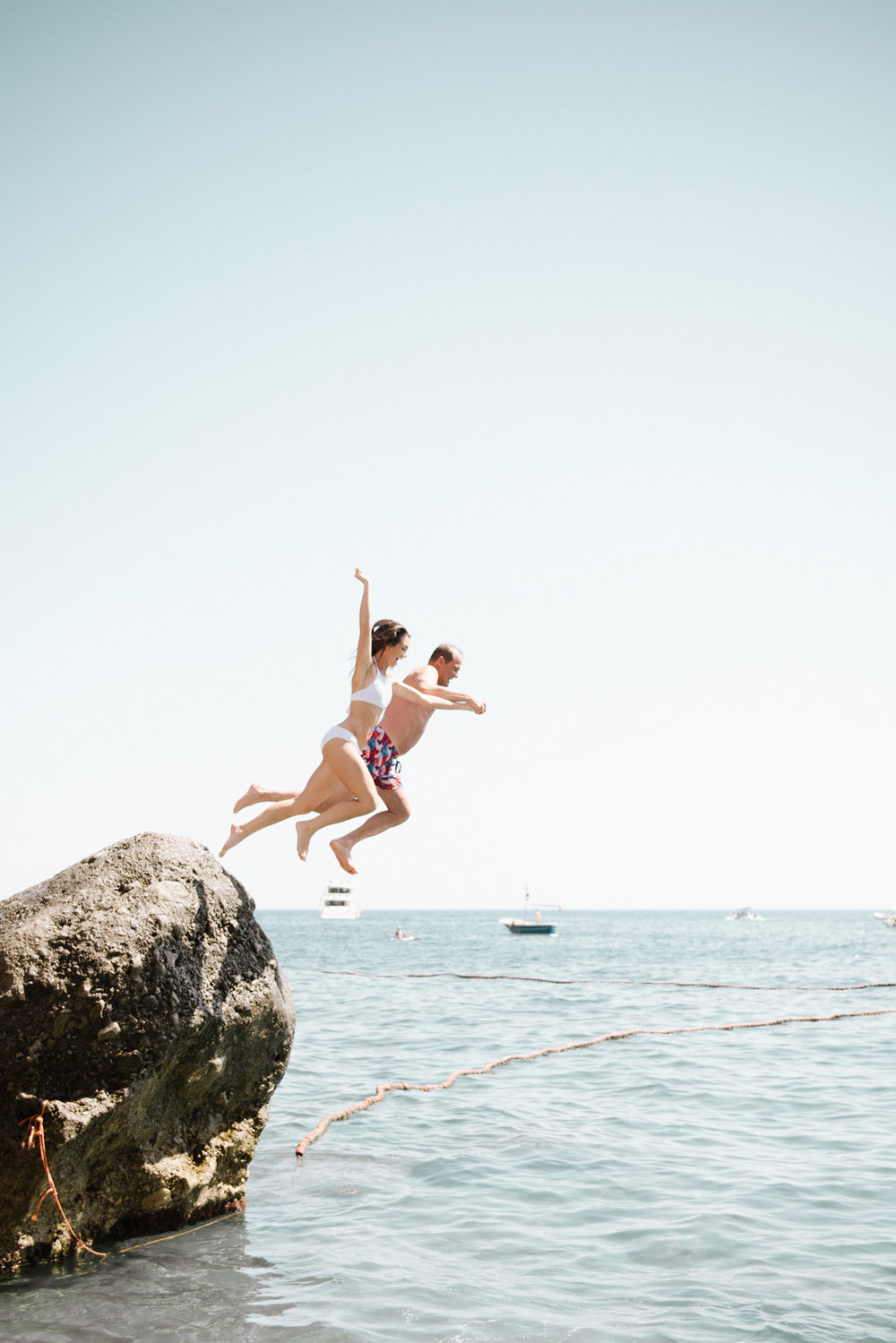 Bride and groom jump off a rock in the Positano marina outside the beach club; Sylvie Gil Photography