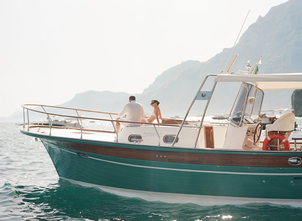 Bride and groom sunbathe on the yacht in the Positano Marina after their wedding brunch; Sylvie Gil Photography