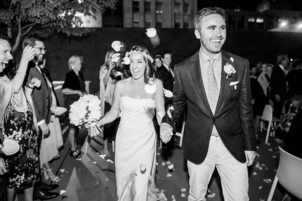 Bride and groom just married, laughing as they walk down the aisle; Sylvie Gil Photography