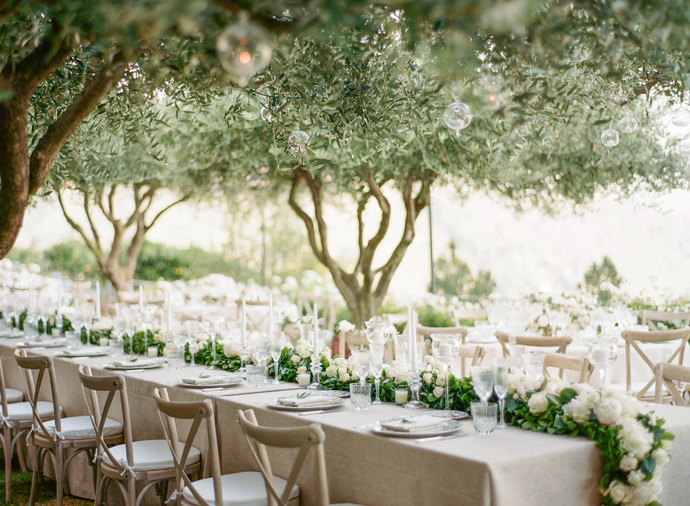 A long floral garland on the wedding reception tables under olive trees in Ravello, Italy.
