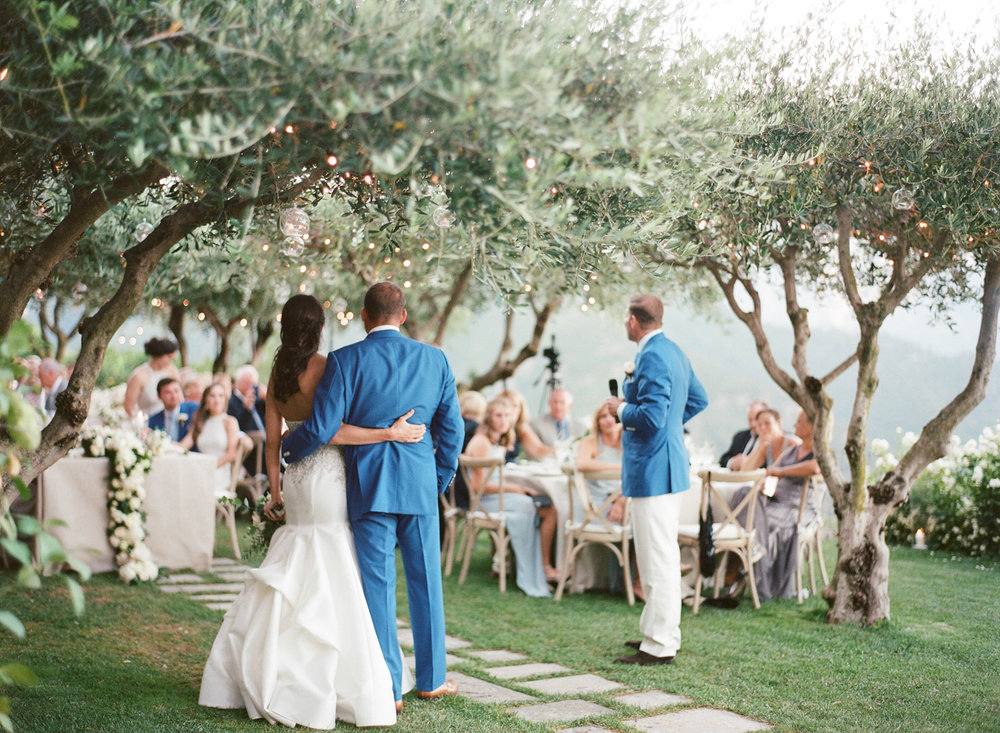 The couple gives a toast under the olive trees at their Amalfi Coast wedding reception; Sylvie Gil Photography