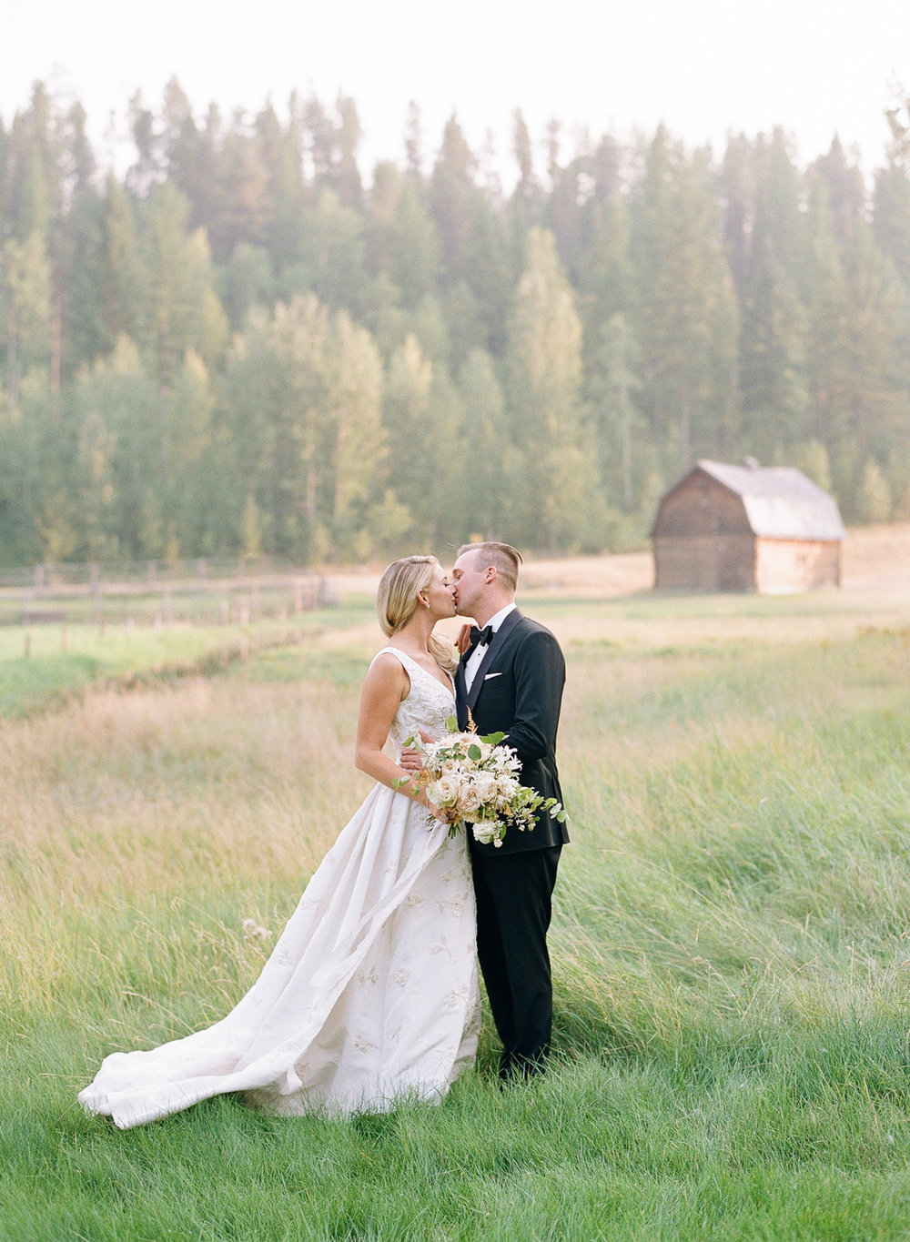 Bride and groom kiss in a meadow near Glacier National Park in Montana; Sylvie Gil Photography