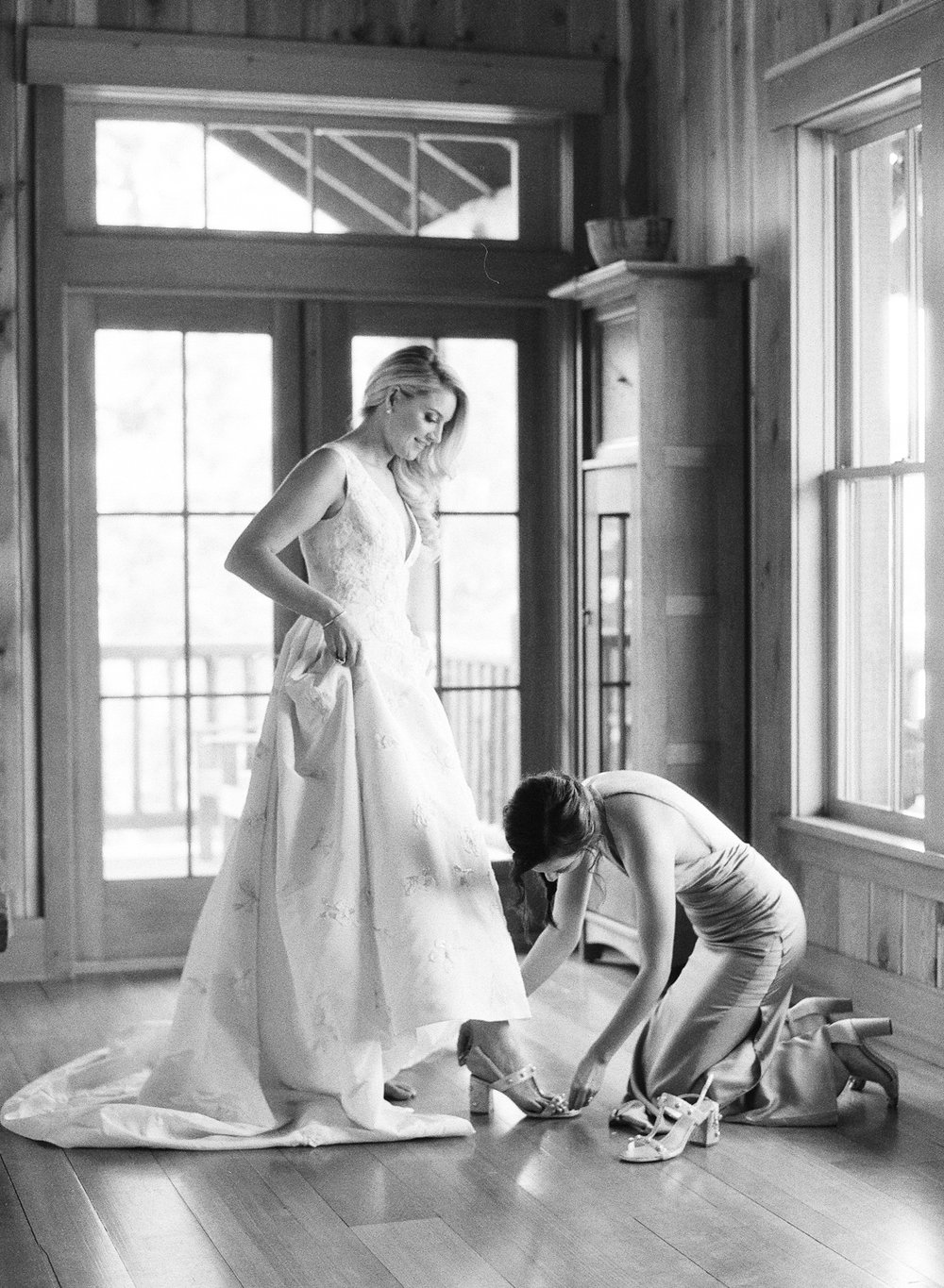 The bride getting ready, putting on shoes with her bridesmaid; Sylvie Gil Photography
