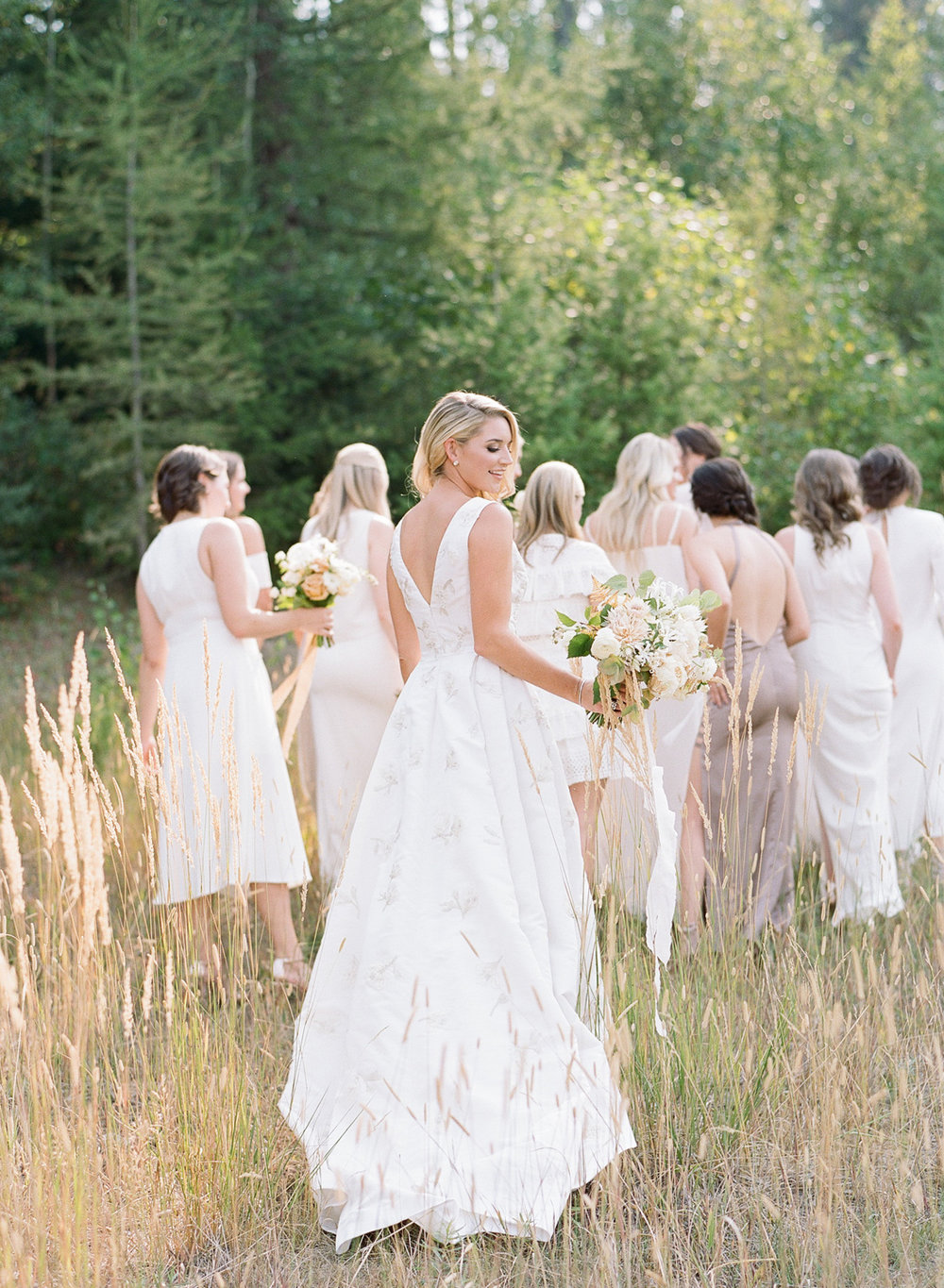 The bride looks over her shoulder during a bridal party shoot in Whitefish, Montana; Sylvie Gil Photography