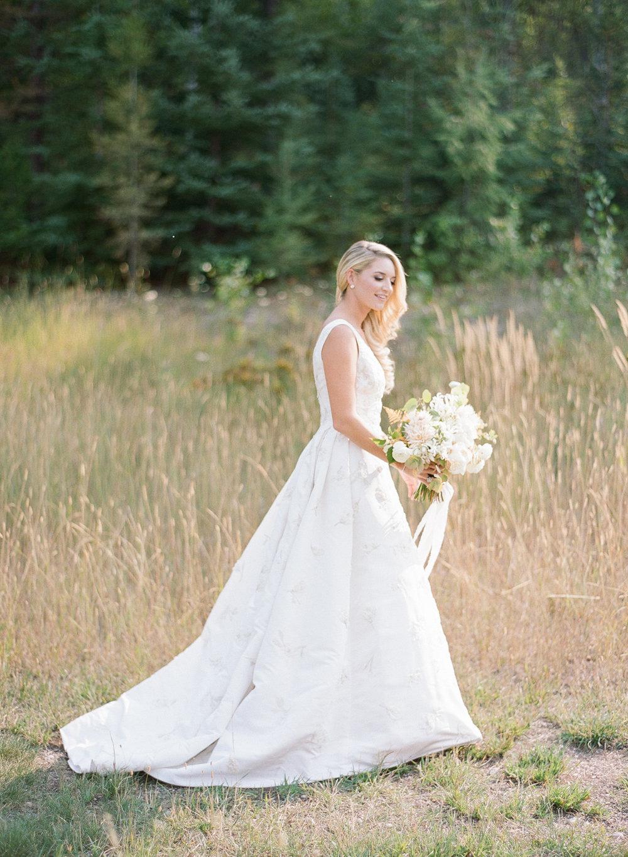 Kaitlin walks through a meadow near Glacier National Park in Montana before her wedding; Sylvie Gil Photography