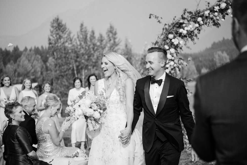 Guests throw rose petals at the couple, just married; Sylvie Gil Photography