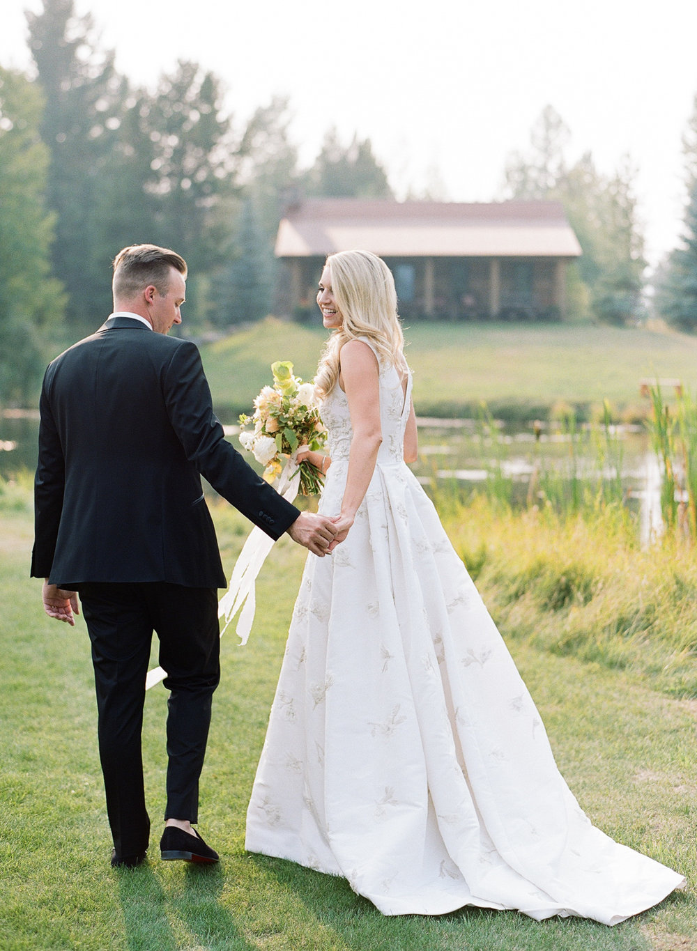 Just married couple walk toward the lodge in Whitefish, Montana; Sylvie Gil Photography