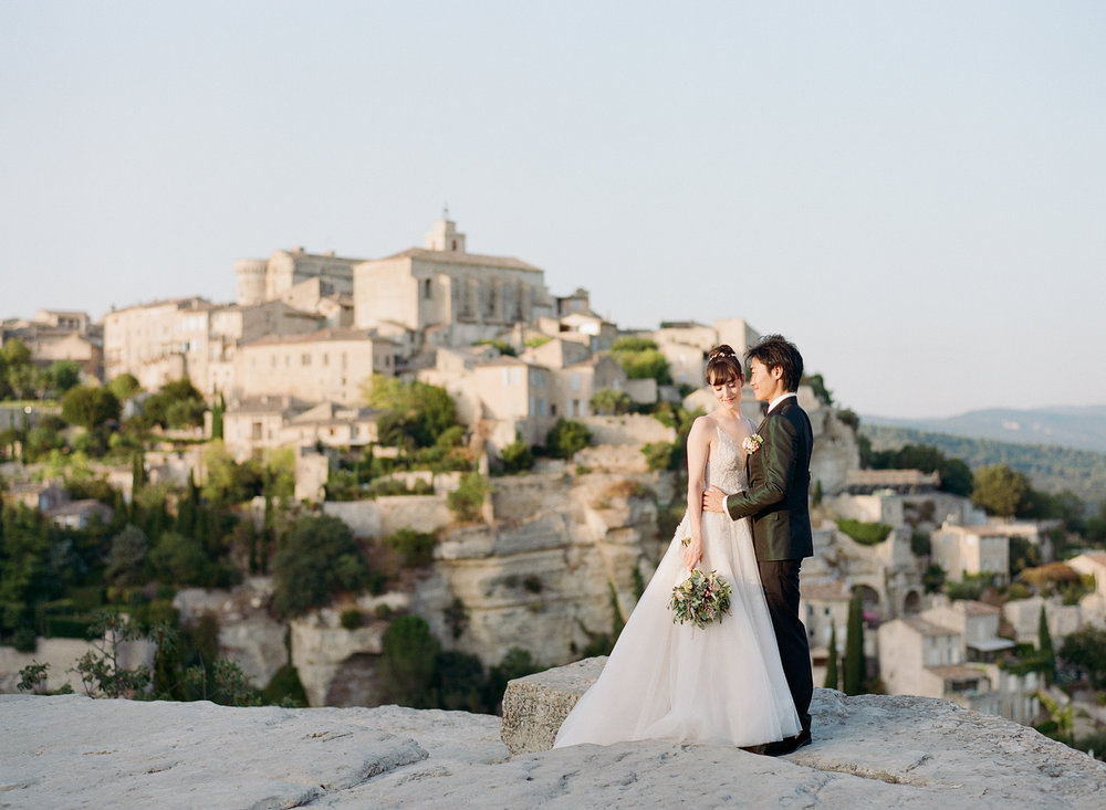 Bride and groom and sunset over the village of Gordes in Provence, France; Sylvie Gil Photography