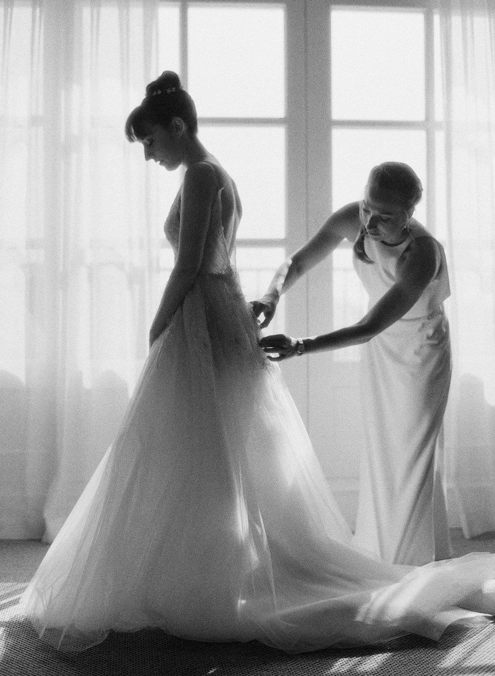 A bridesmaid helps zip up the bride's fairytale ball gown; Sylvie Gil Photography