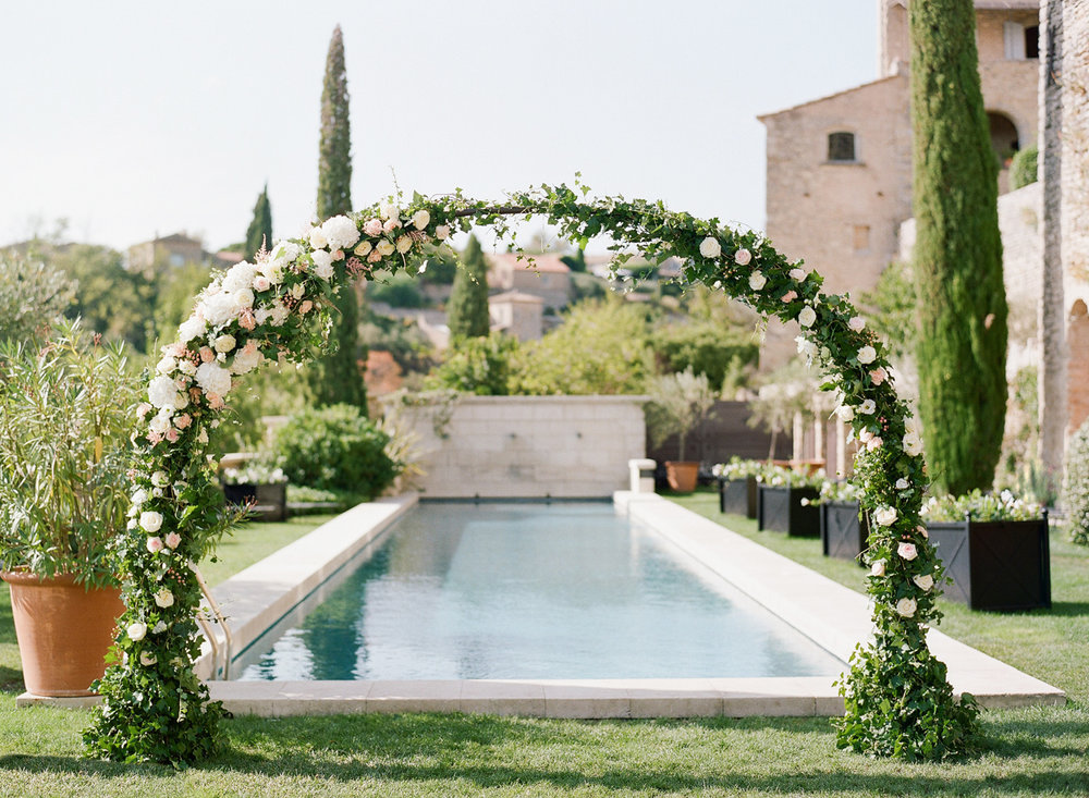 A floral arch in the wedding ceremony space in Provence, France; Sylvie Gil Photography