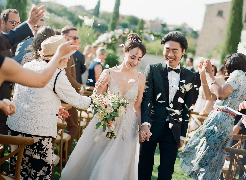 Just married couple walks down the aisle, guests throw rose petals; Sylvie Gil Photography