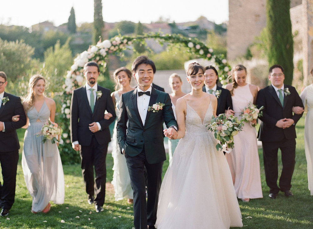 The bridal party walks arm in arm outside the chateau in Gordes, France after the wedding ceremony; Sylvie Gil Photography
