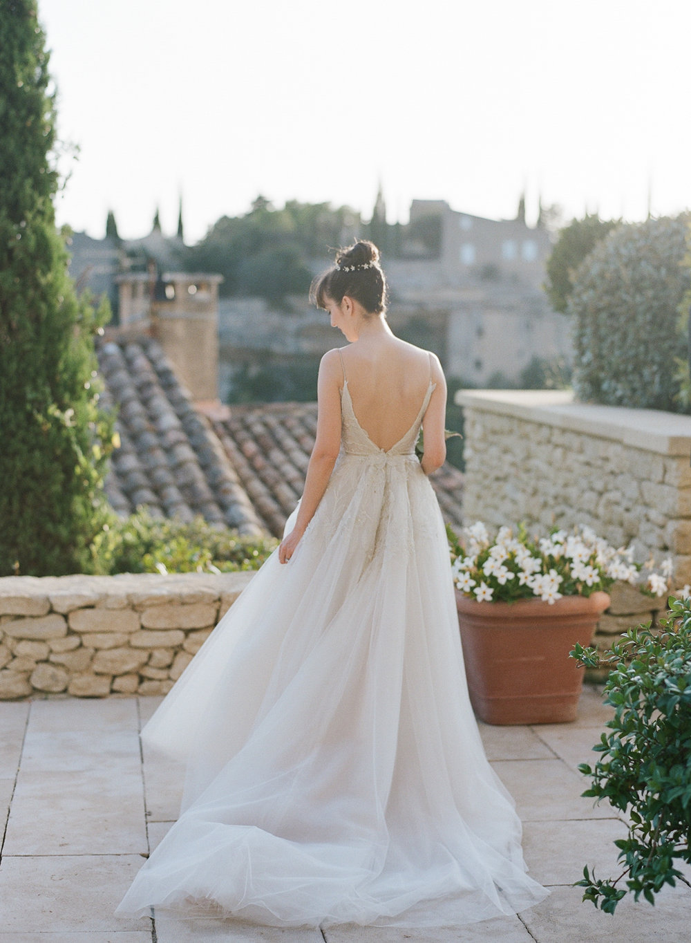 Bride stands on the patio of a chateau in Gordes, France at sunset; Sylvie Gil Photography