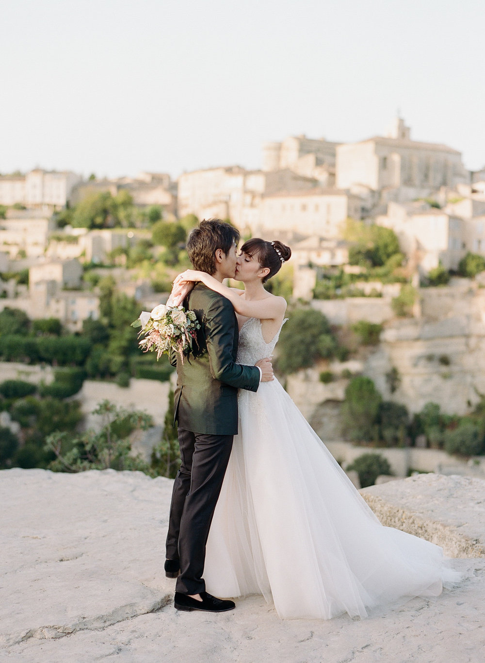 Bride and groom kiss on a hill above Gordes, France, just married; Sylvie Gil Photography