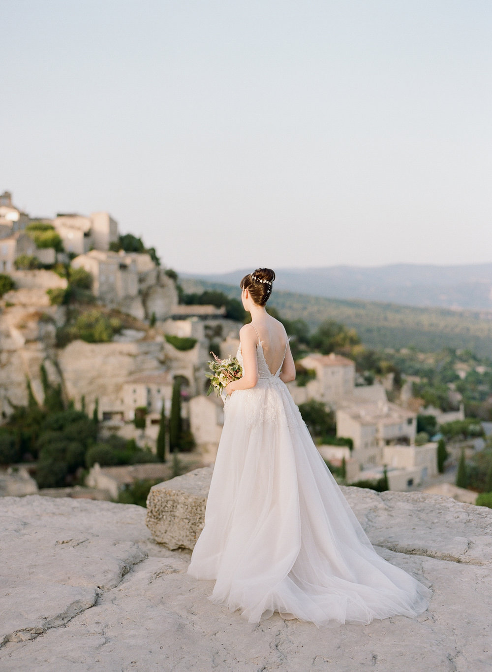 The bride in her fairytale ball gown looks out over the vineyards and village of Gordes, France; Sylvie Gil Photography