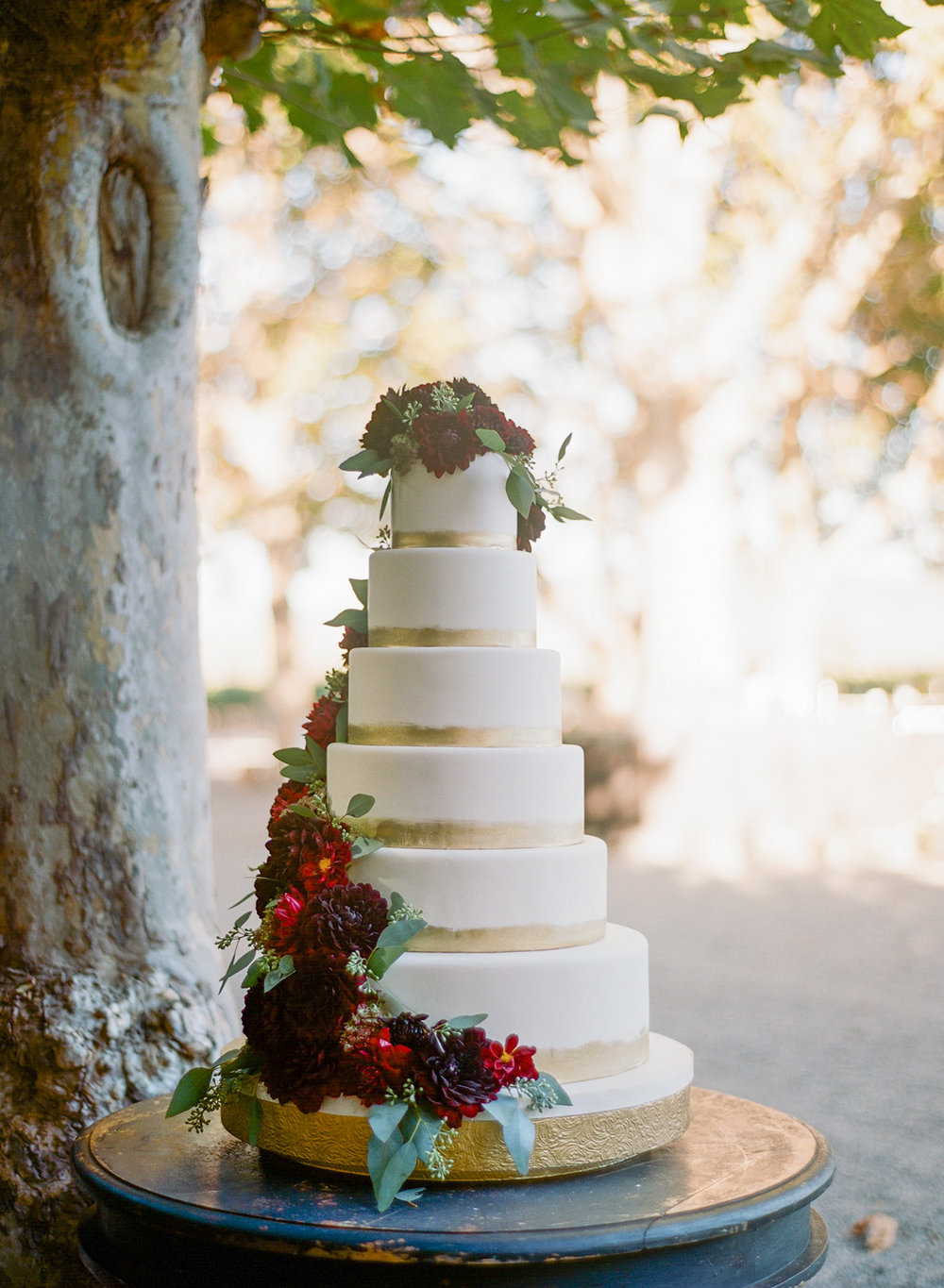 A six-tier, gold-trimmed wedding cake decorated with burgundy dahlias and eucalyptus leaves; Sylvie Gil Photography