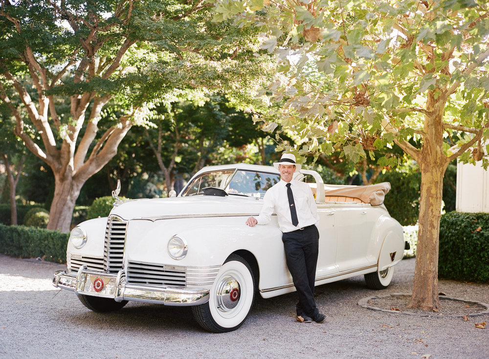 A vintage white convertible getaway car for a wedding at Beaulieu Gardens in St. Helena; Sylvie Gil Photography