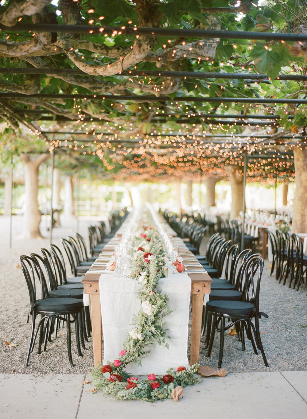 Long reception tables decorated with eucalyptus floral garlands; Sylvie Gil Photography