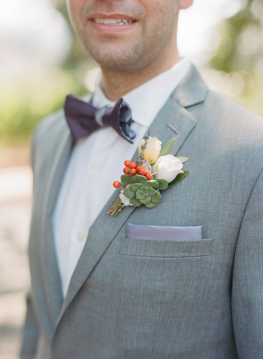 One of the grooms' succulent boutonnieres and pocket square; Sylvie Gil Photography