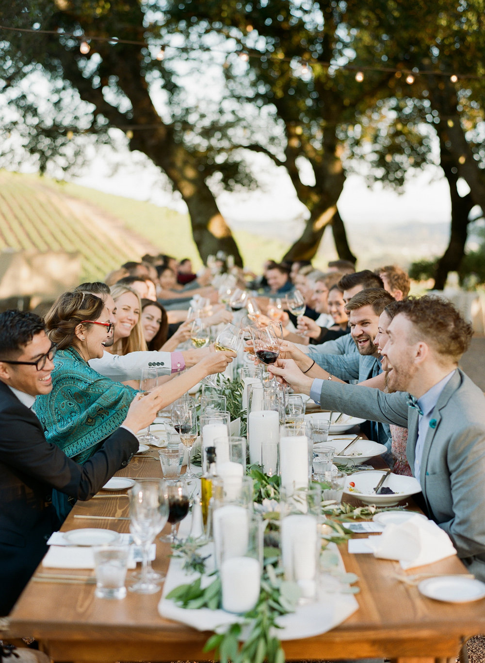 Guests toast the newly married couple at long tables at Kunde Winery in Napa Valley; Sylvie Gil Photography