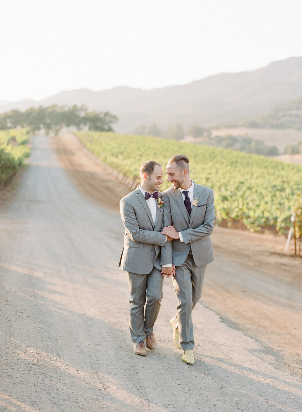 The grooms walk through the vineyard at Kunde Winery at sunset after their wedding; Sylvie Gil Photography