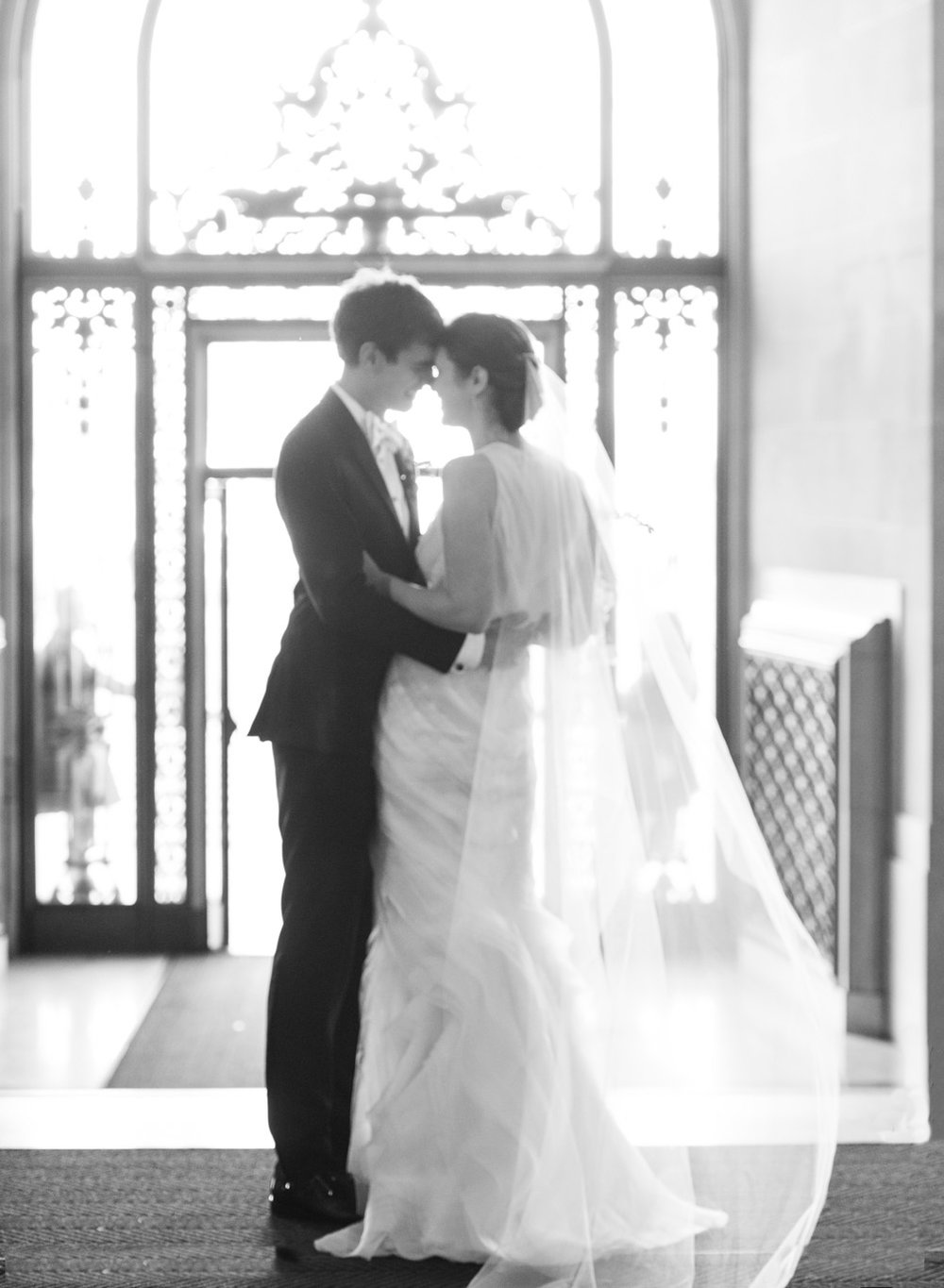 Just married, Jill & Brian stand in the foyer of San Francisco City Hall; Sylvie Gil Photography