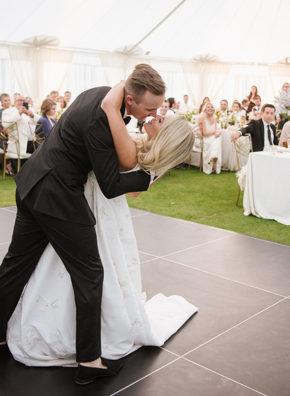 The bride and groom dip during the first dance for a kiss; Sylvie Gil Photography