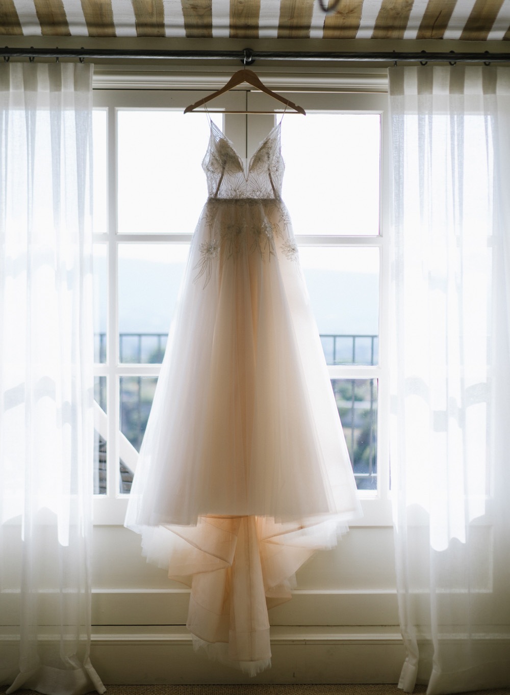 The bride's translucent fairytale ball gown hangs in a window; Sylvie Gil Photography