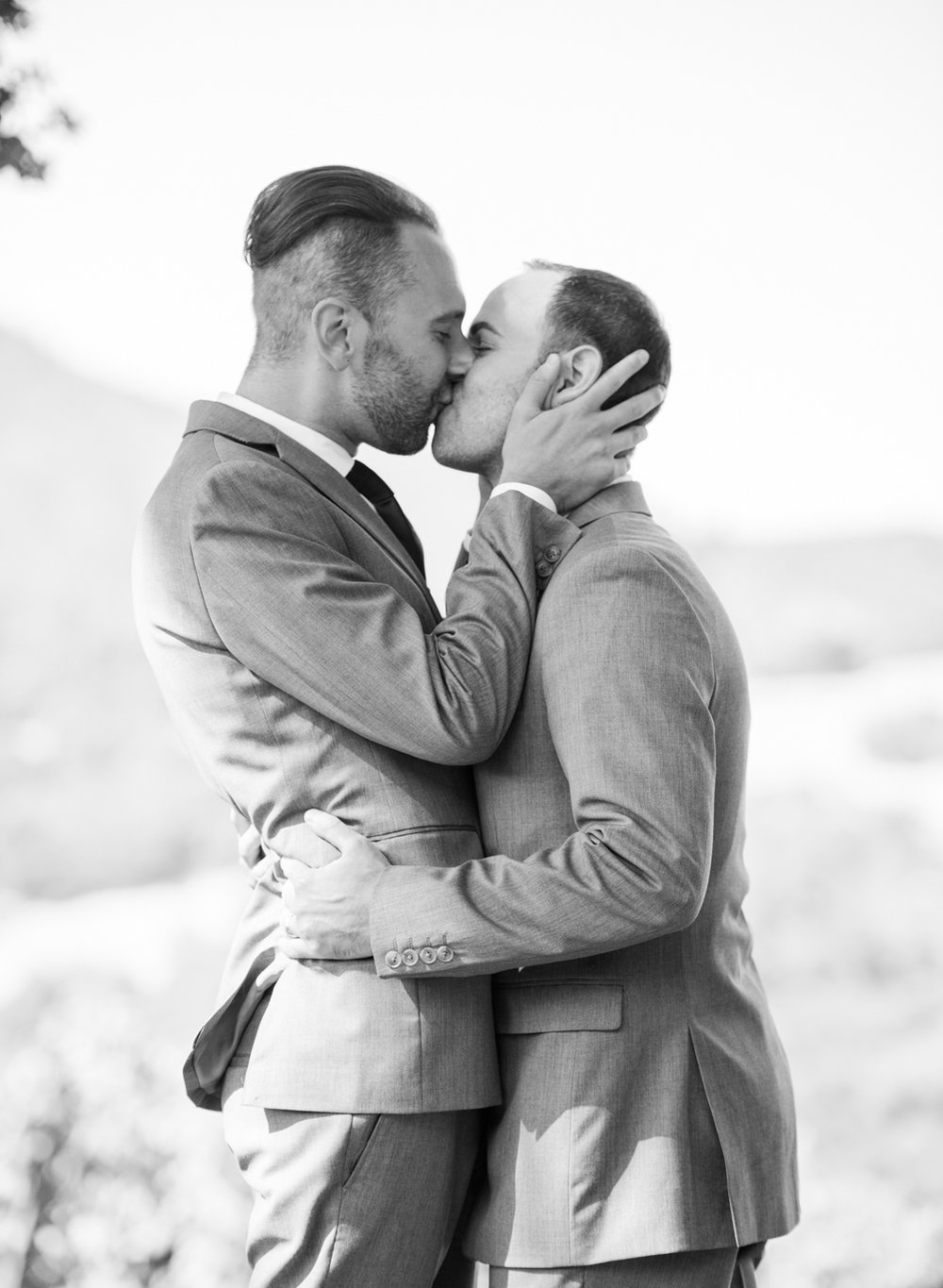 Grooms share their first kiss during their Kunde Winery wedding ceremony; Sylvie Gil Photography