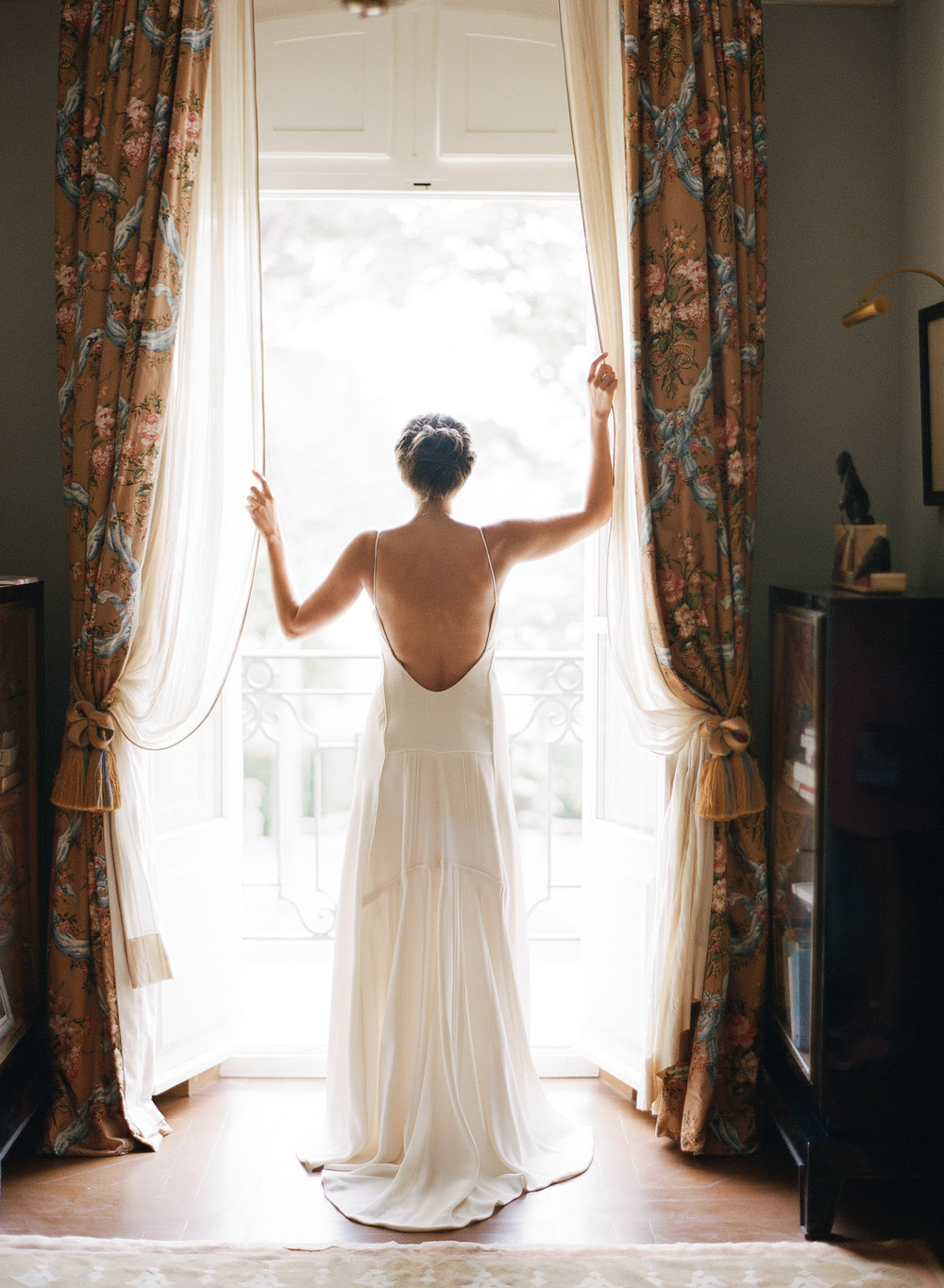 The bride stands at the window of the chateau getting ready; Sylvie Gil Photography